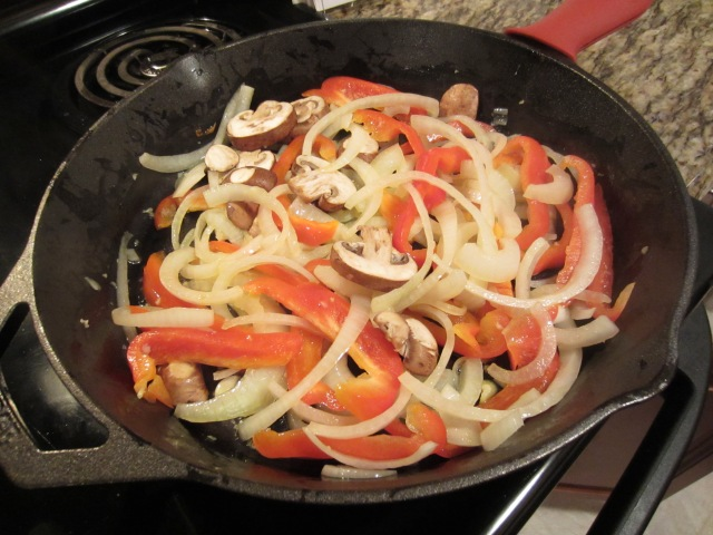 onions, red peppers, and mushrooms in cast iron skillet
